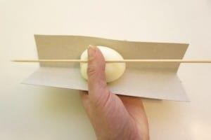 Položiti jaje unutar karton, staviti preko njega štapić...