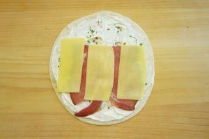 Premazati tortilje sirnim namazom, složiti pršut i sir